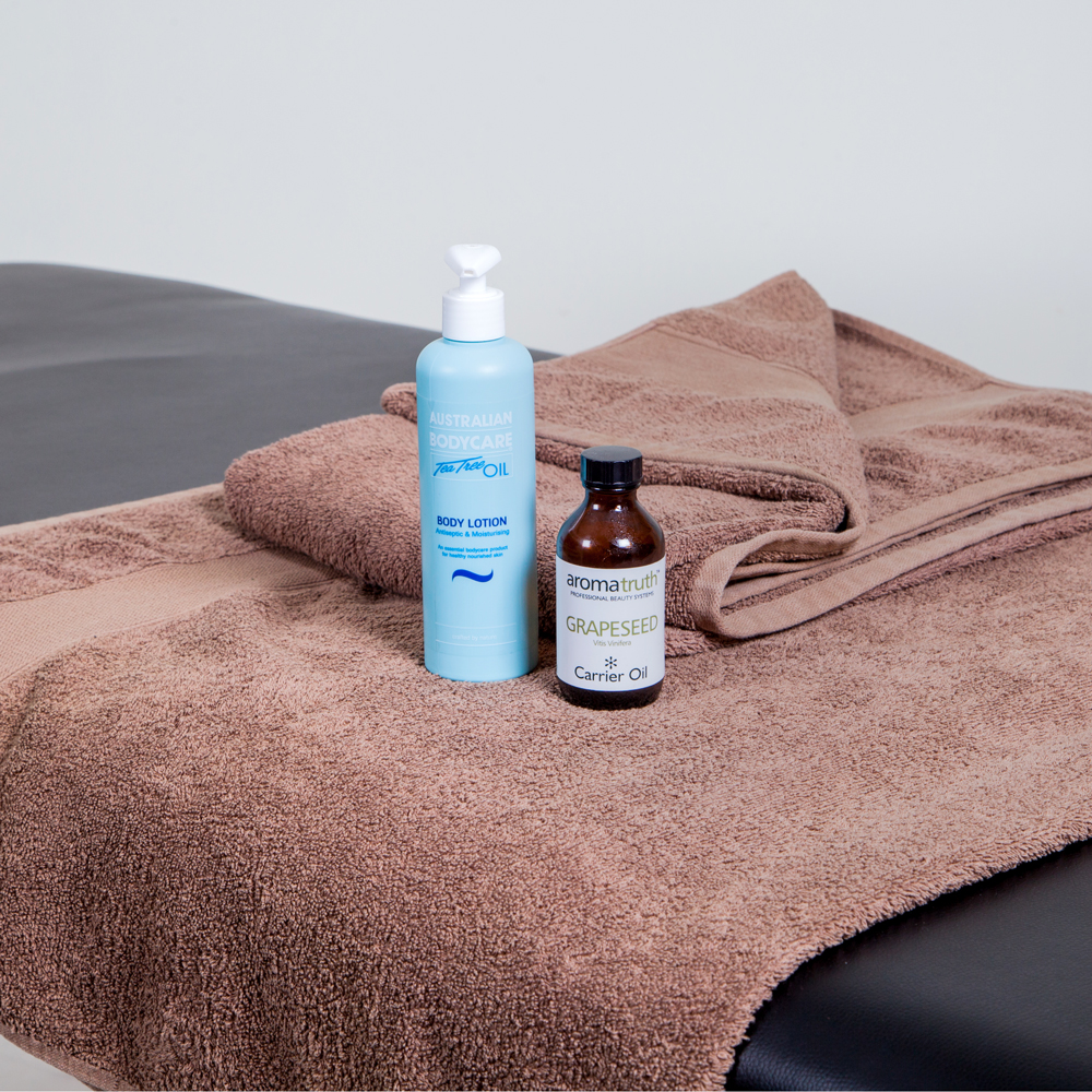2 massage oils positioned on a towel laying on a massage bed